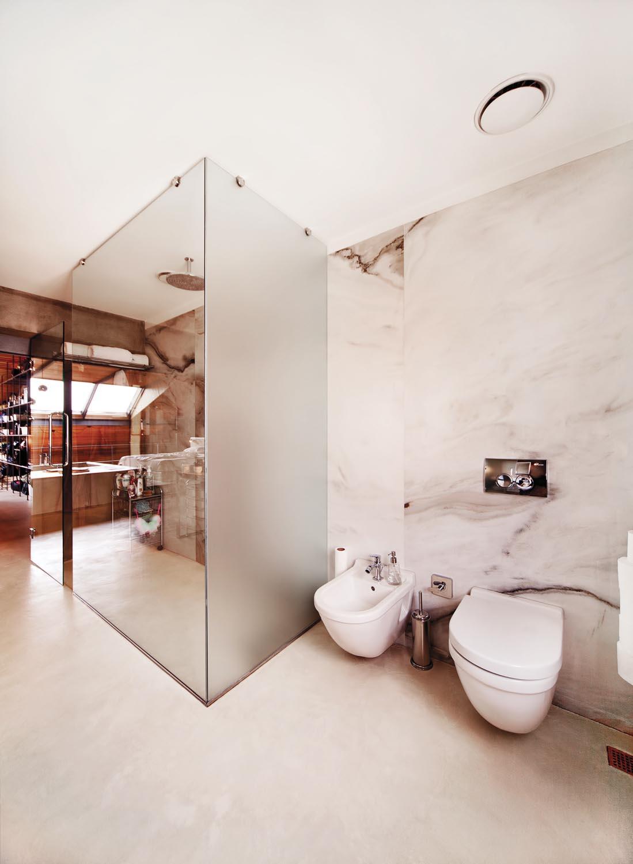 Marble walls create a luxe feel in a minimalist bathroom