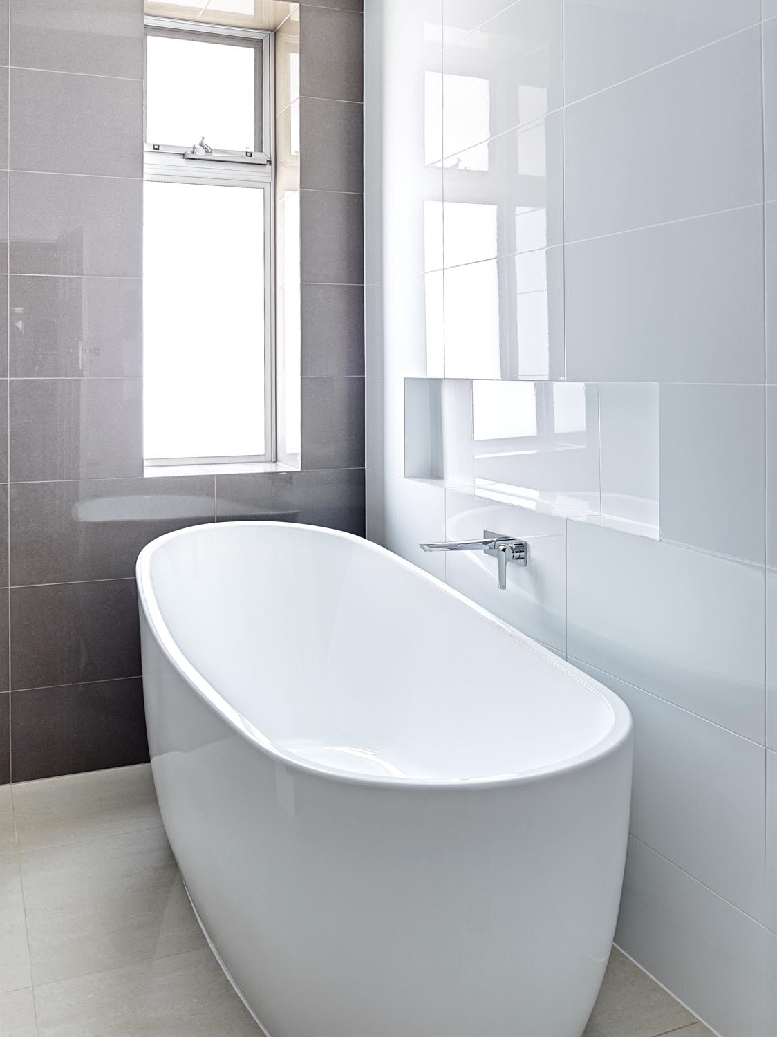 The dark, large-format tiles, with white gloss tiles for the side walls, creates a sense of grandeur