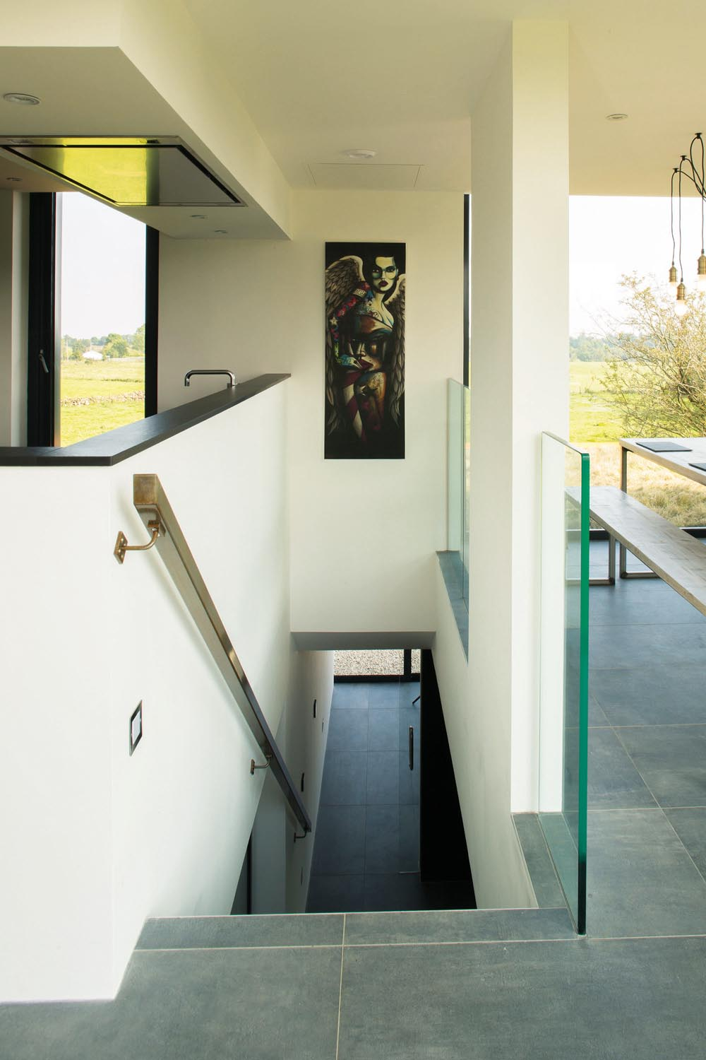 Stairs lead down to the sleeping area, while glass balustrades add to the sense of space and light