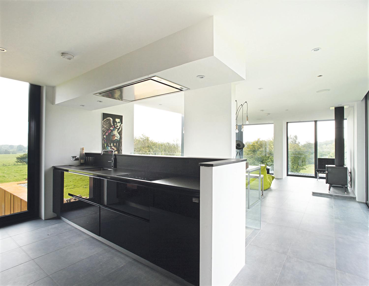 Dark gloss units define the kitchen and allow the view to remain the focus