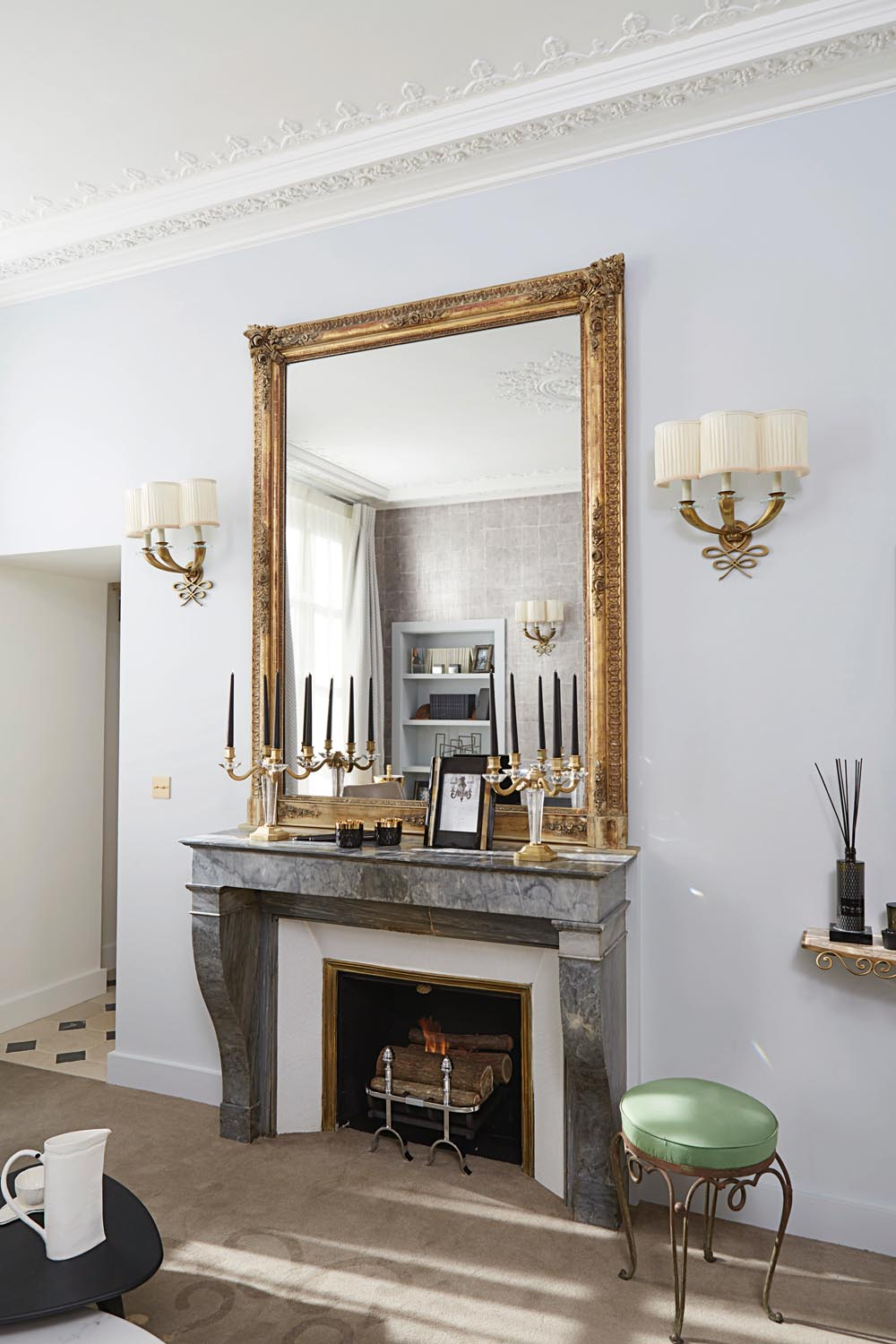 A gold-framed mirror sitting atop a stone fireplace is a throwback to '40s perfection