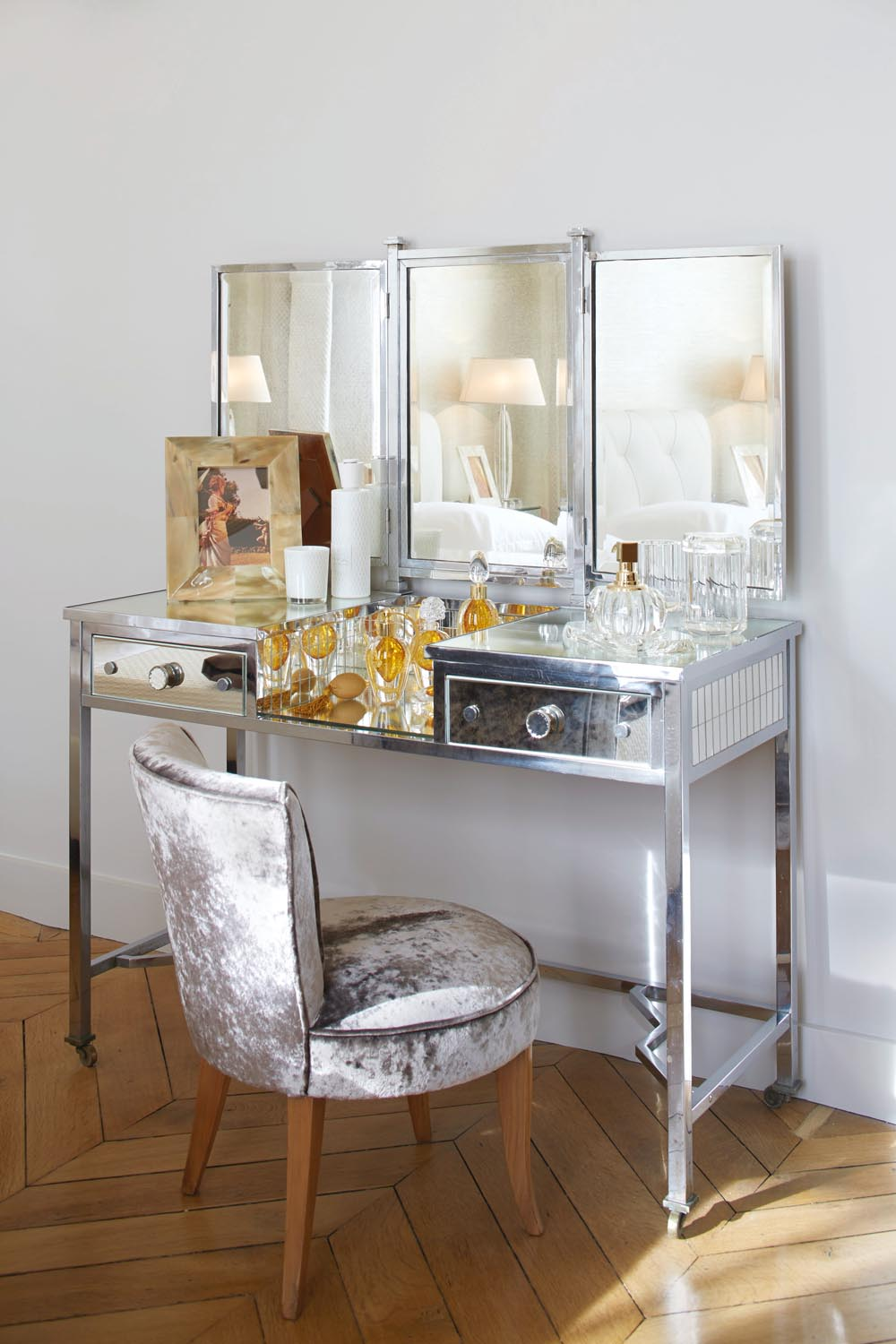 A three-mirror silver dressing table adds a luxe metallic feel to a crisp white bedroom