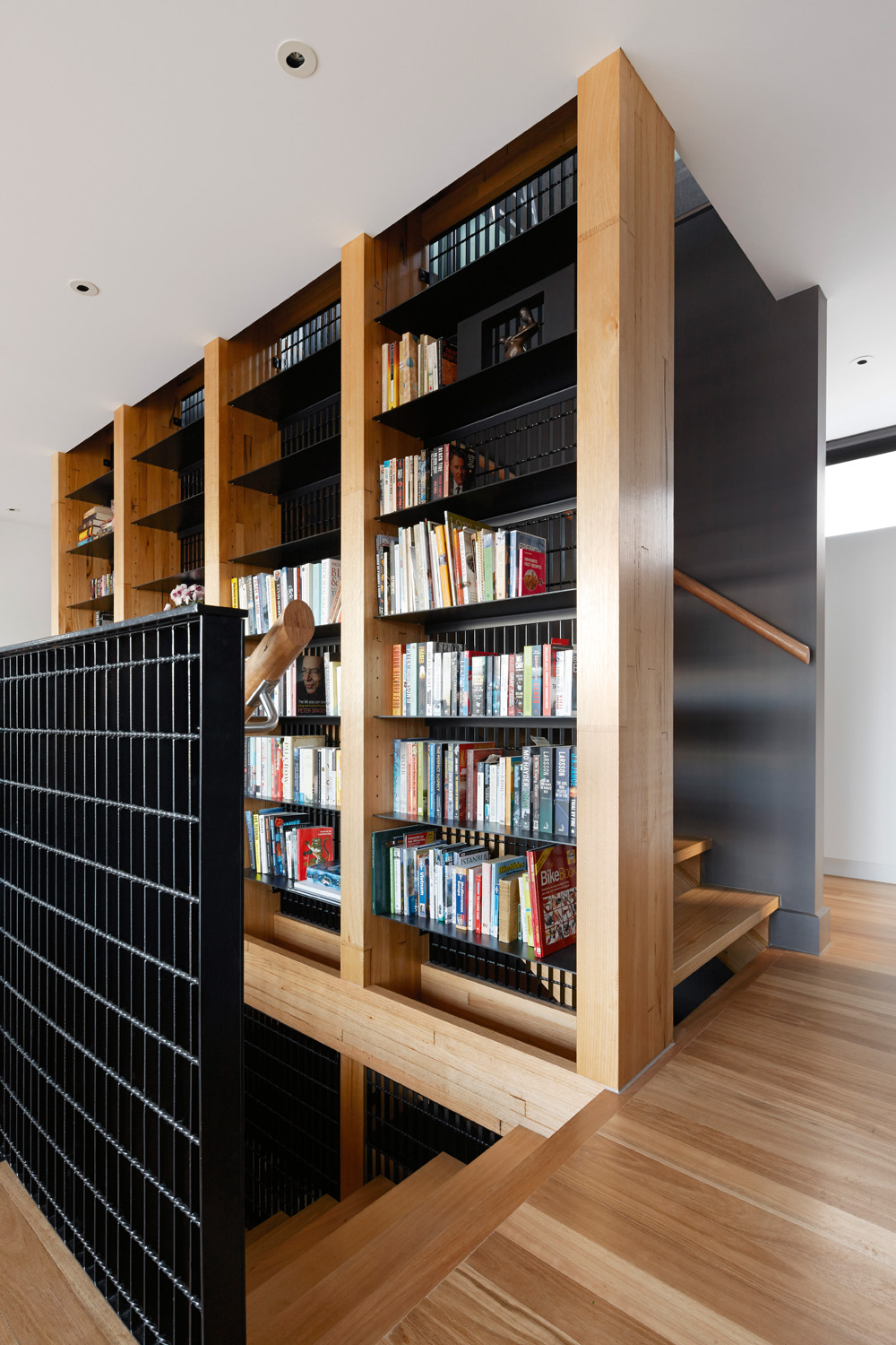 A bookcase between staircases mixes up the space