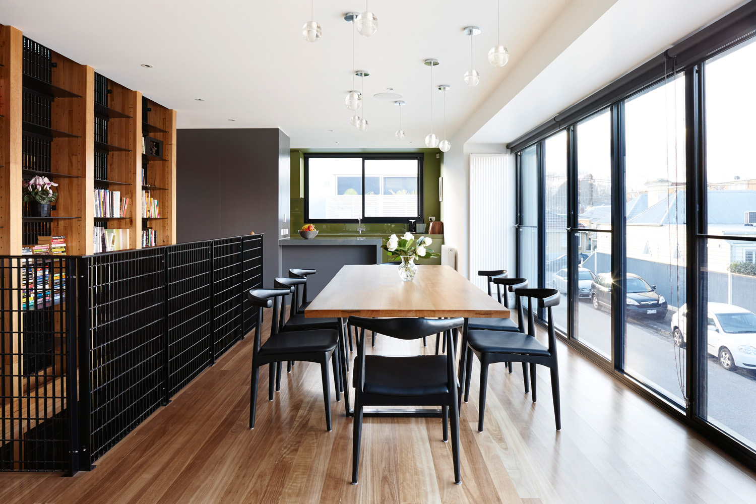 Dark-coloured chairs create contrast against warm timber
