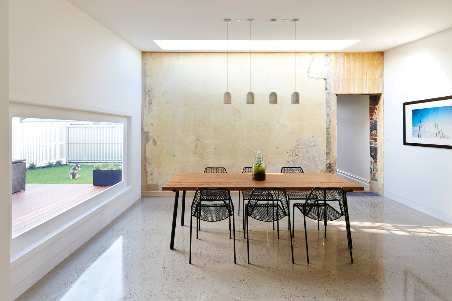 An exposed concrete feature wall brings a gritty element to the clean and modern design