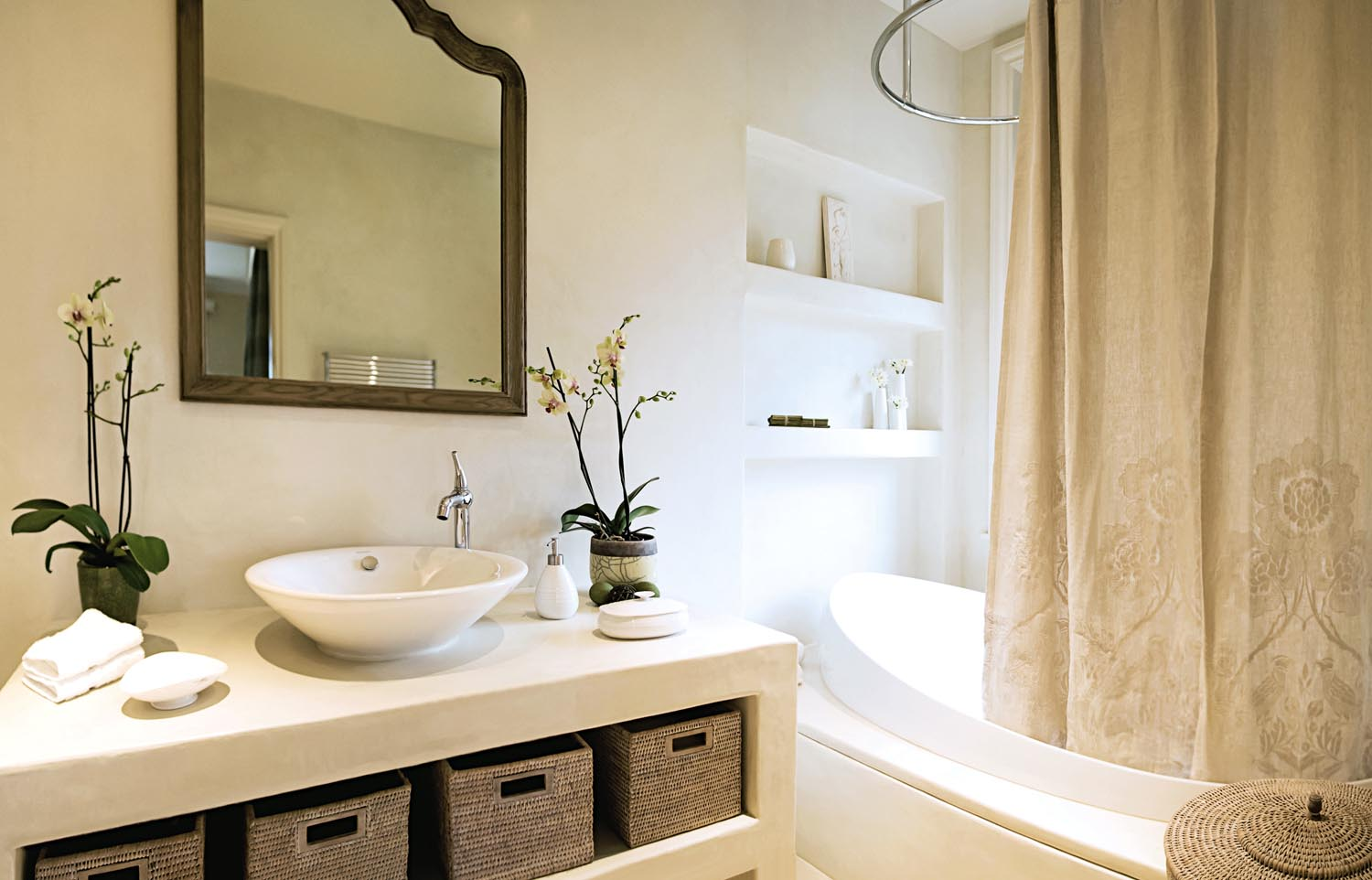 Textural elements such as the storage  baskets add interest to a simple bathroom