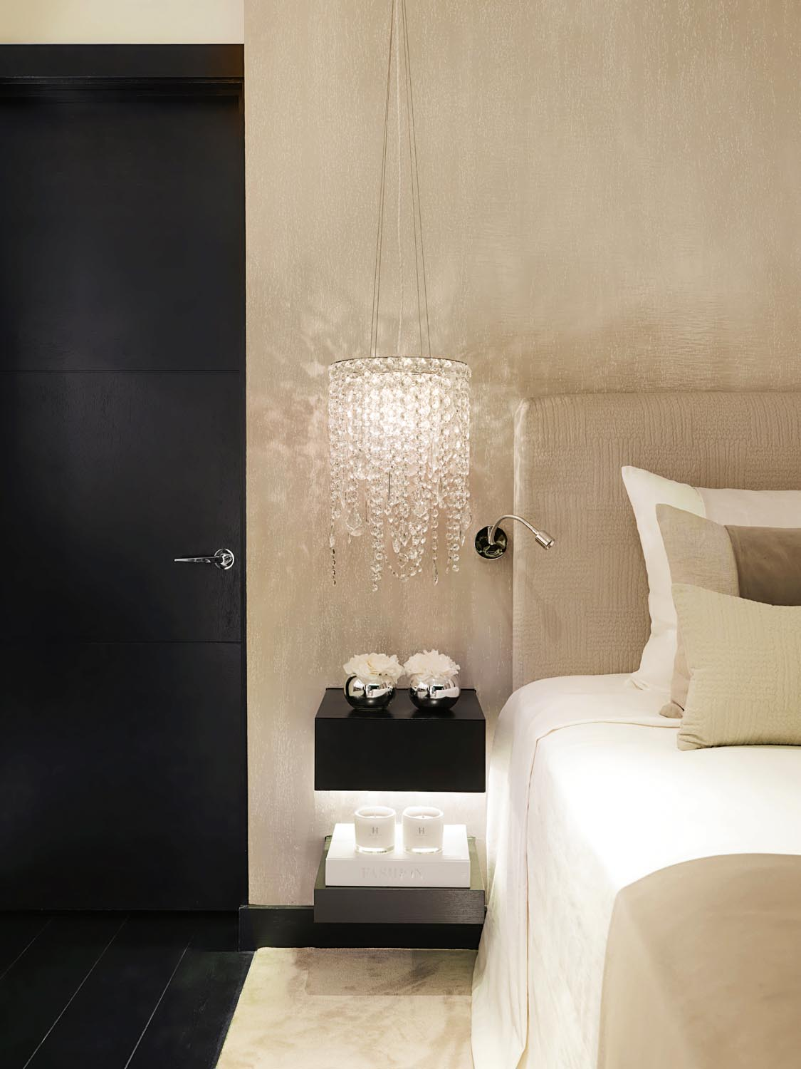A chandelier besides the bed creates instant glamour