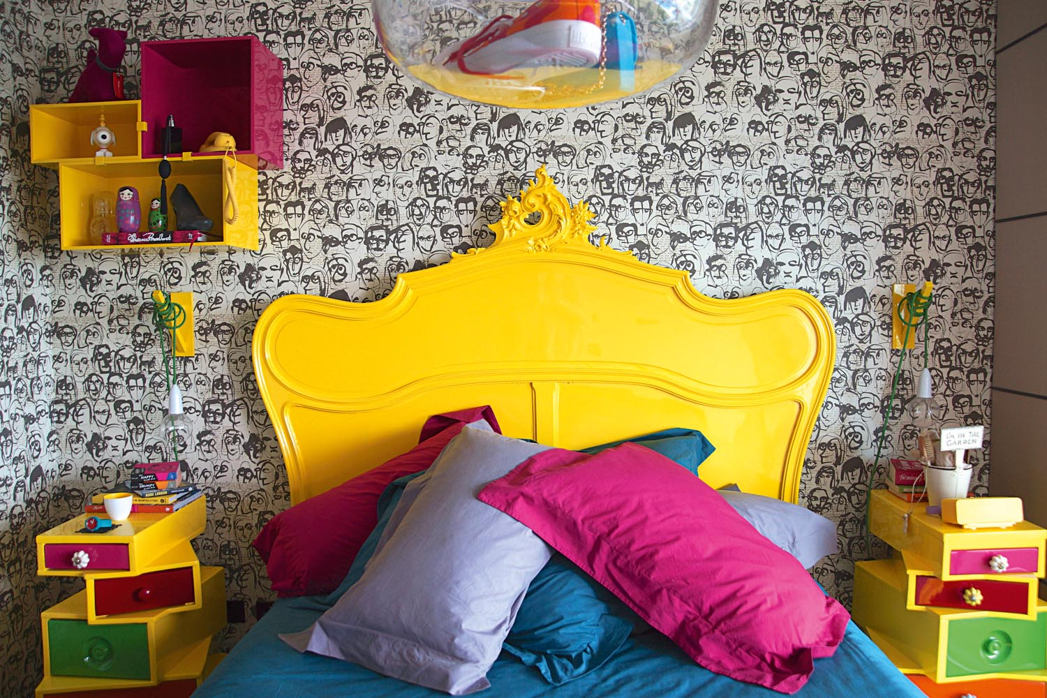 This room is all about the energy, clashing bright colours against the monochromatic wallpaper