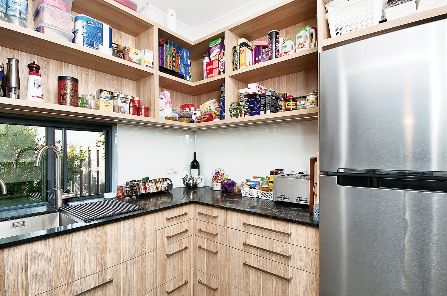 A simple kitchen with open pantry and a silver fridge