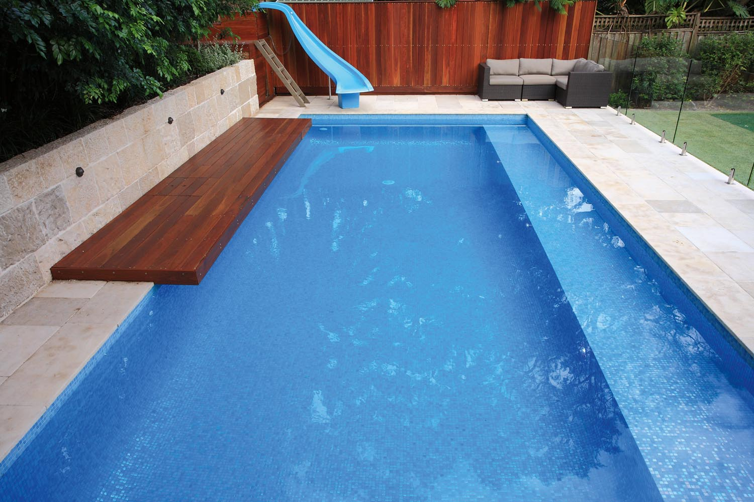 A blue pool with a wooden bench and a water slide