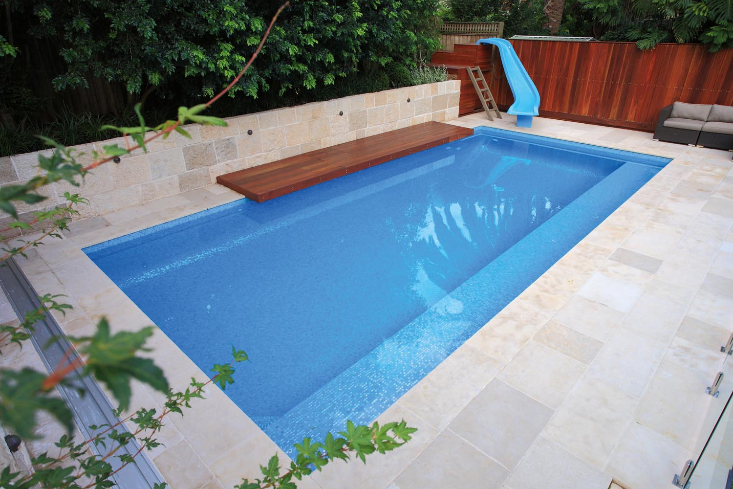 A modern blue pool with a water slide and outdoor furniture surrounded by plants
