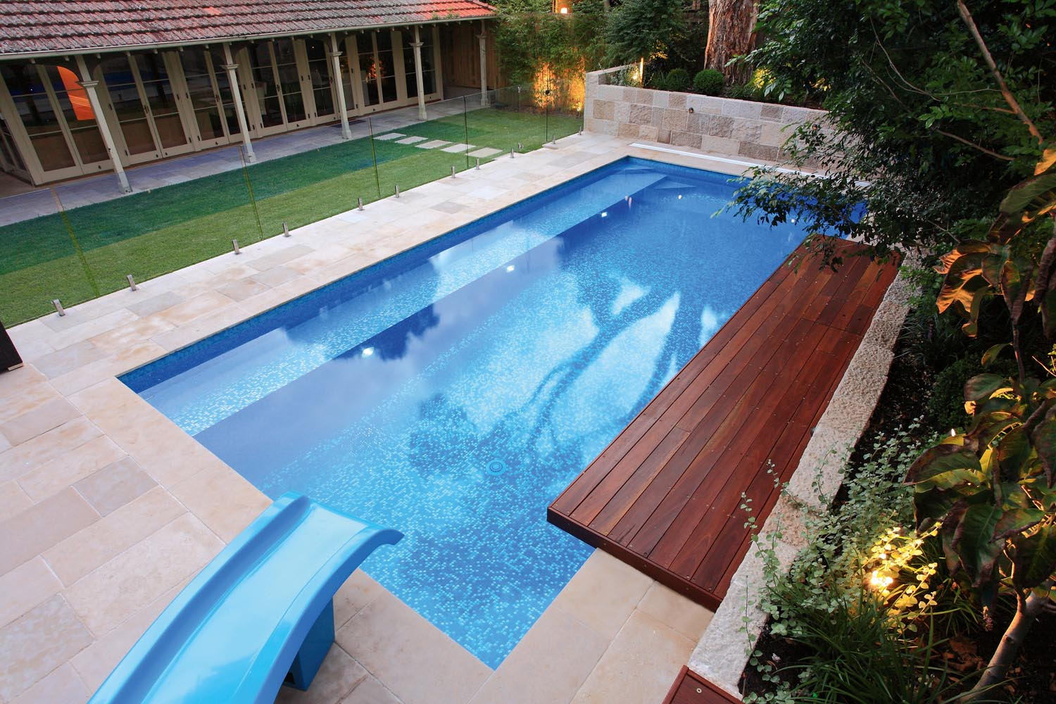 A modern pool view from above with a bench and a water slide