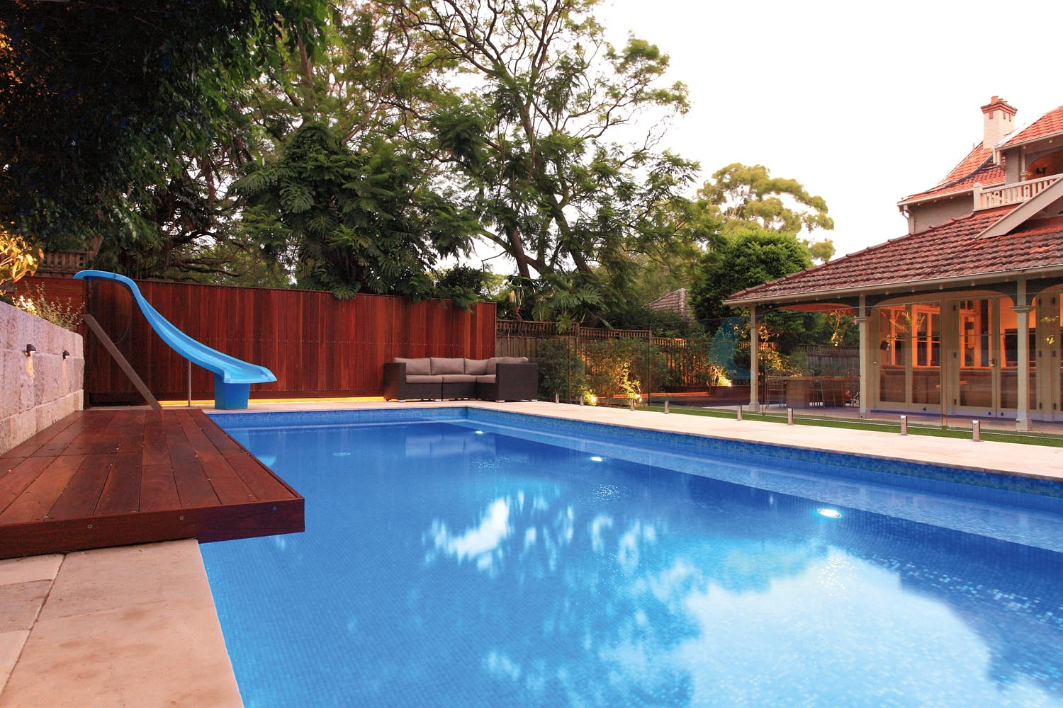 A modern blue pool next to a house with outdoor furniture and a water slide