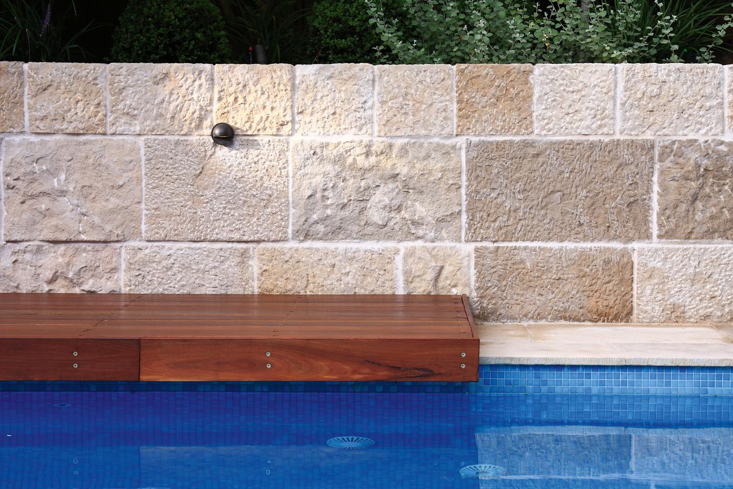 Modern pool closeup with a wooden bench