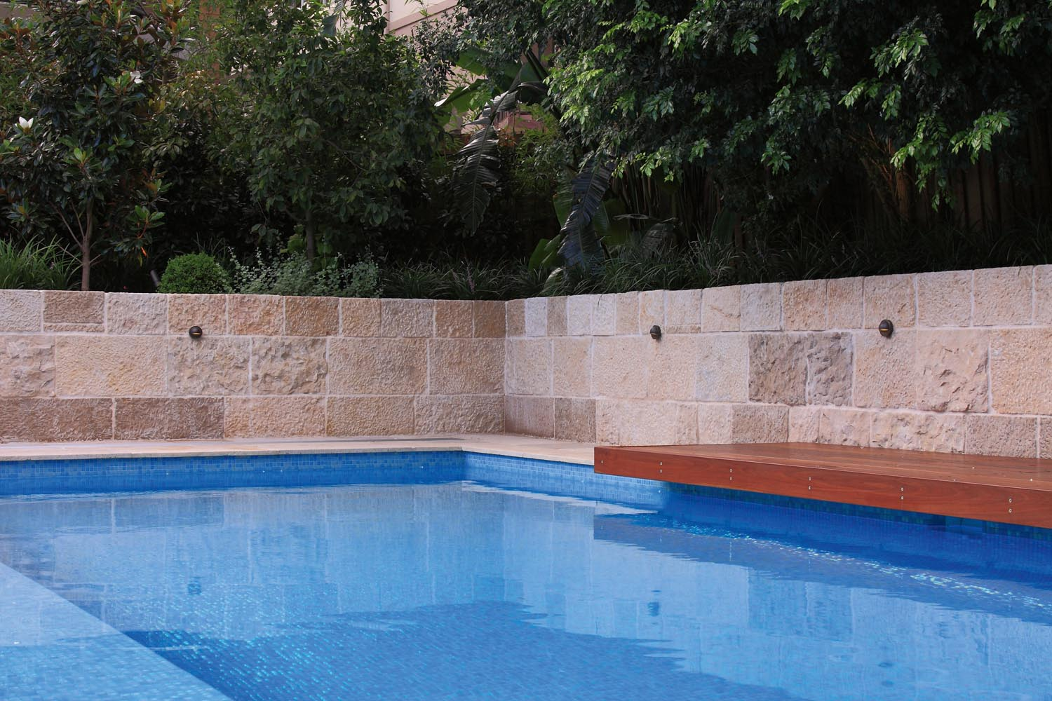 A modern pool next to a wall and a bench