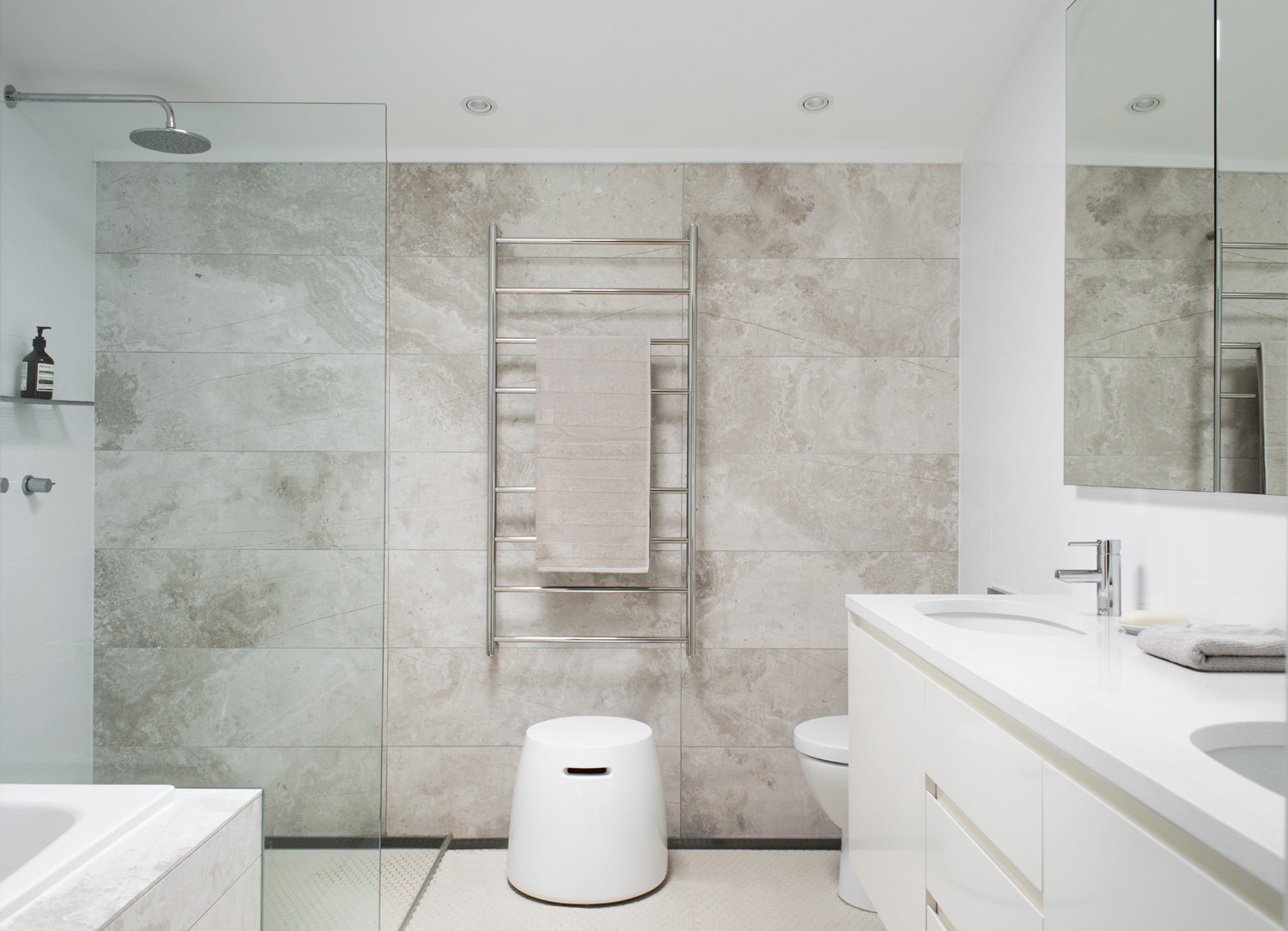 A tiled feature wall evokes depth in a white bathroom
