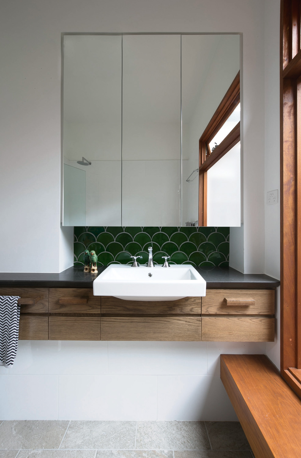 Green fish scale tiles bring a natural aspect to the bathroom