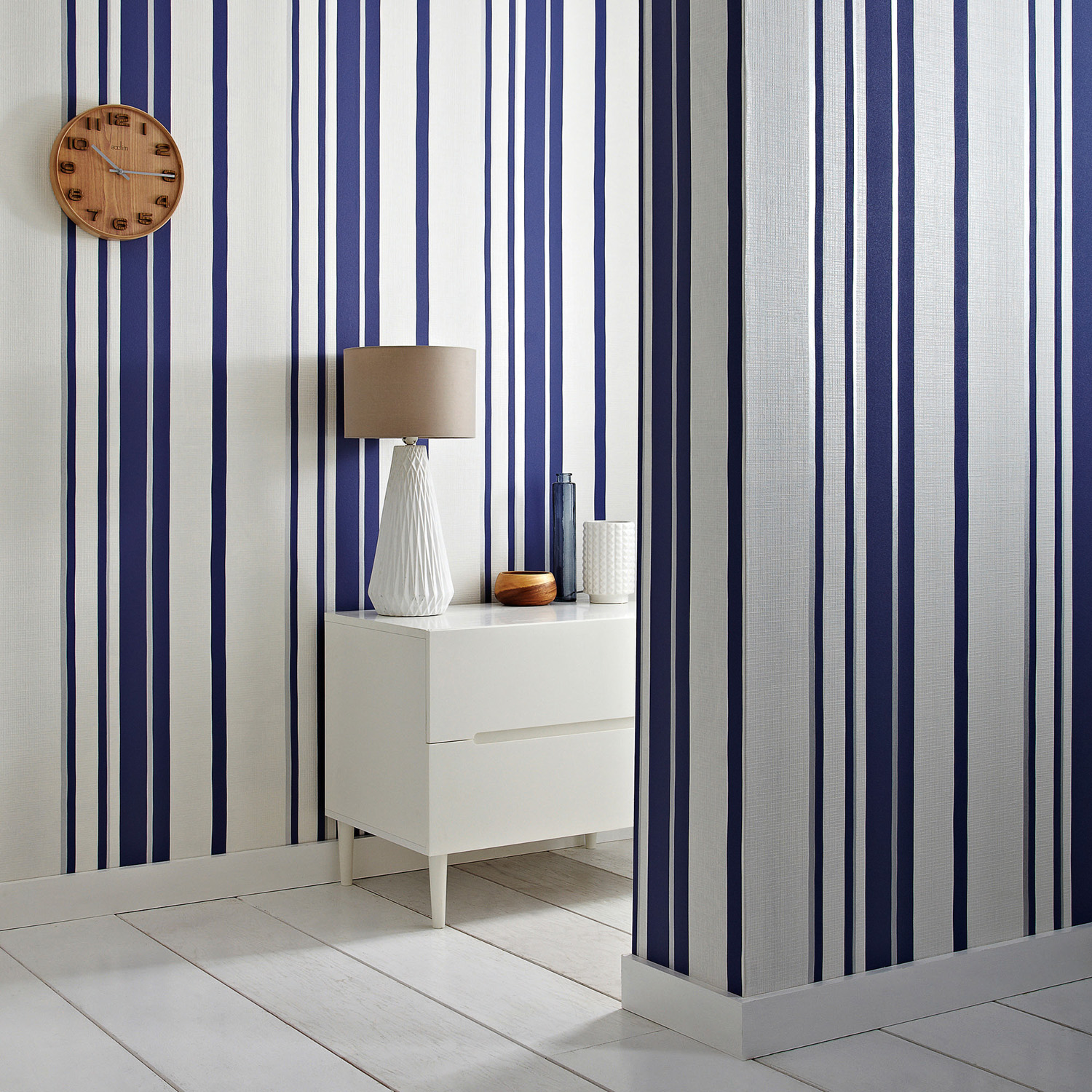 Expand a small space or create the illusion of high ceilings with the Hoppen Stripe wallpaper in white and Prussian blue from GRAHAM & BROWN. The white stripes are textured with a linen effect while a subtle silver strip lines either side, making it pop. grahambrown.com/uk