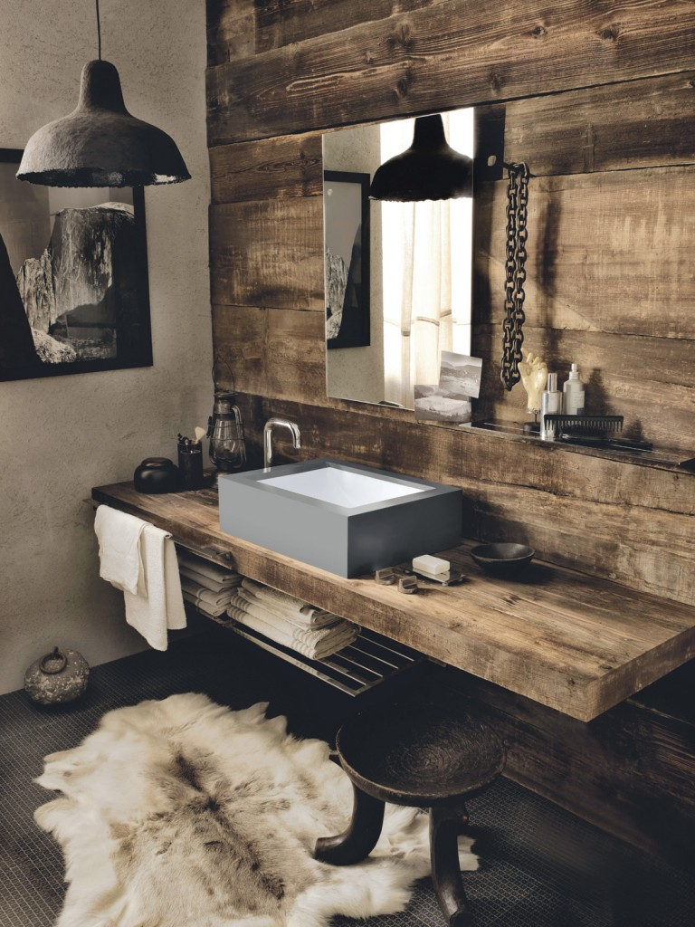 Smoothly set into Corian in the industrial grey Deep Cloud shade, the Corian Refresh washbasin offers a touch of contemporary chic to the wooden vanity top's rough texture, providing an unexpected twist to a rustic ambience.