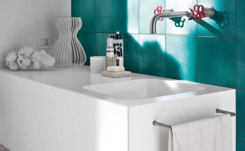 Bathed in Mediterranean sunlight, artisan-style aquamarine tiles contrast with the velvety smooth touch of a Corian Serenity basin set into a Corian Glacier White vanity top. The space evokes the fresh fragrance of a bright summer morning by the sea.