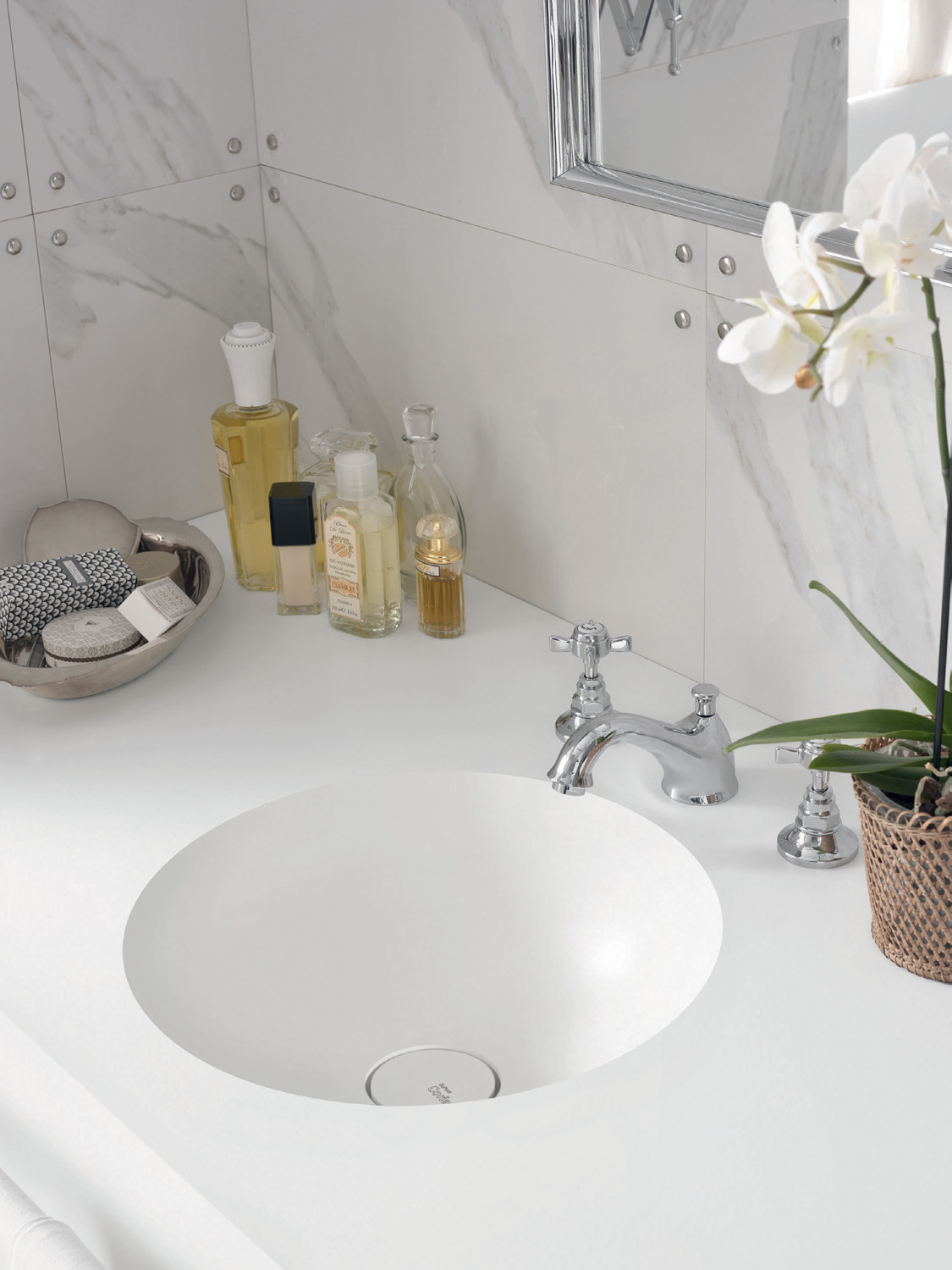 Inspired by 1950s Italian design, the use of marble in this setting is reminiscent of the spacious interiors of a mansion. Seamlessly incorporated into a cantilevered vanity top in Corian Glacier White, a pair of Corian Purity washbasins emphasise the refined atmosphere of this bathroom.