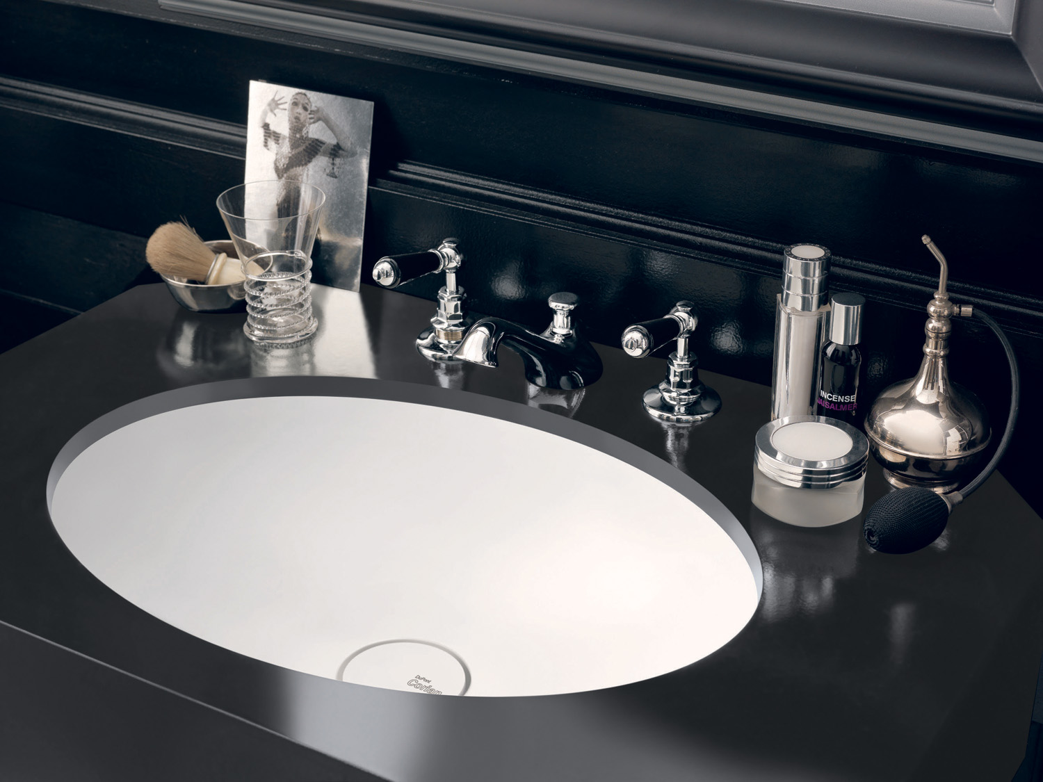 Integrated into a jet-black mount made from Corian Deep Nocturne, the sleek Corian Relax washbasin works in crisp contrast with the dark wall panelling and chequerboard tiled floor to evoke a timeless elegance.