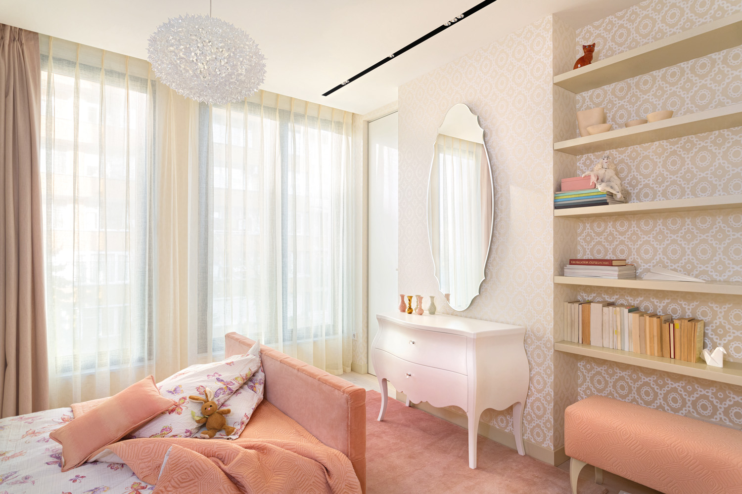 A feminine room is created using soft pinks and patterned wallpaper