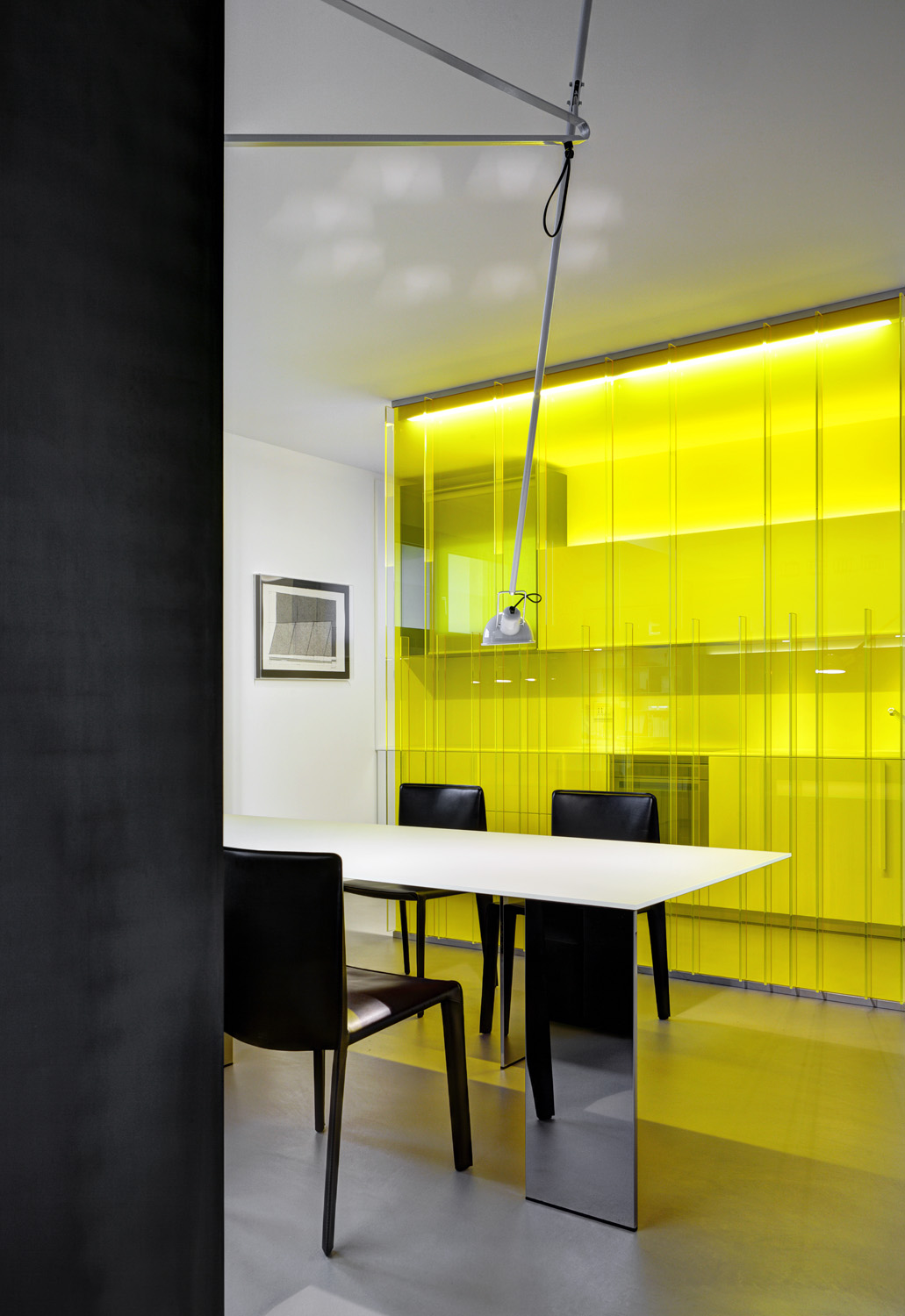 Yellow glass separates the kitchen and dining areas