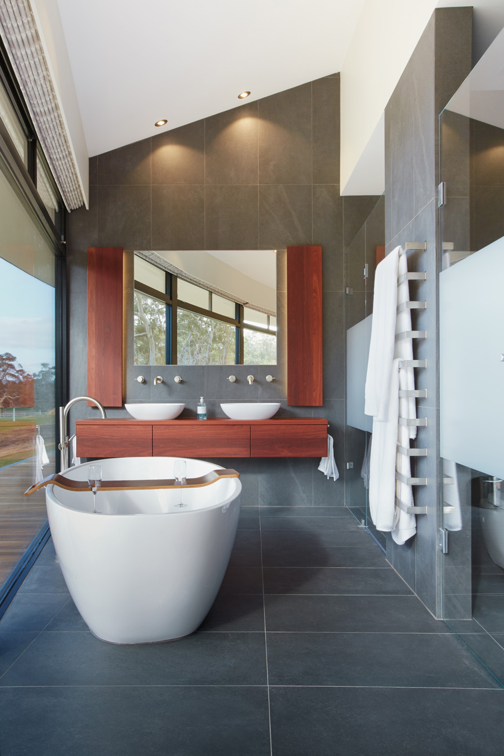 A freestanding tub by the window is made for relaxation