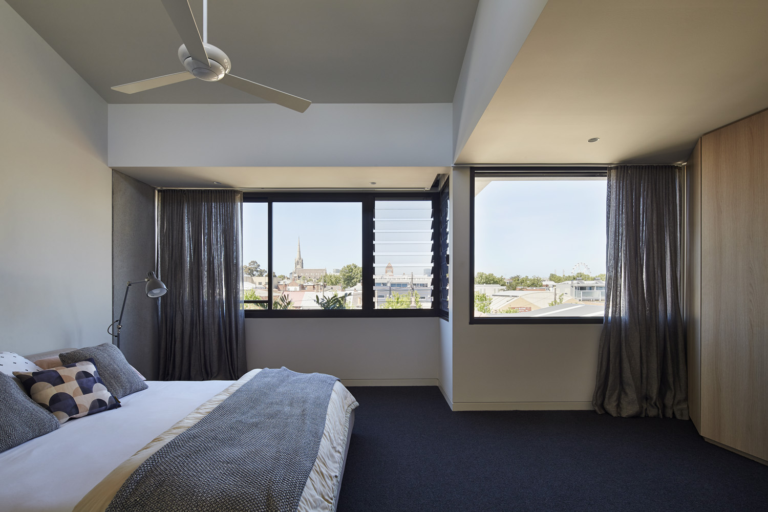 Natural light floods the bedroom, which is ideal when using a darker interior scheme