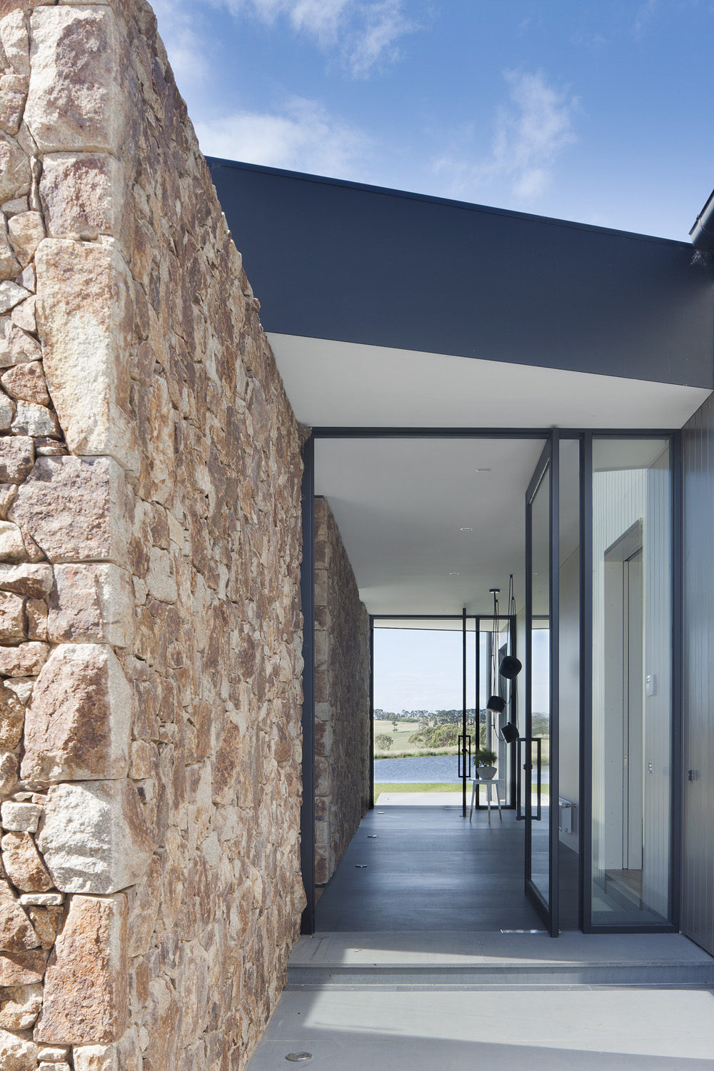 A natural stone wall adds a rustic element to the home's interior and exterior