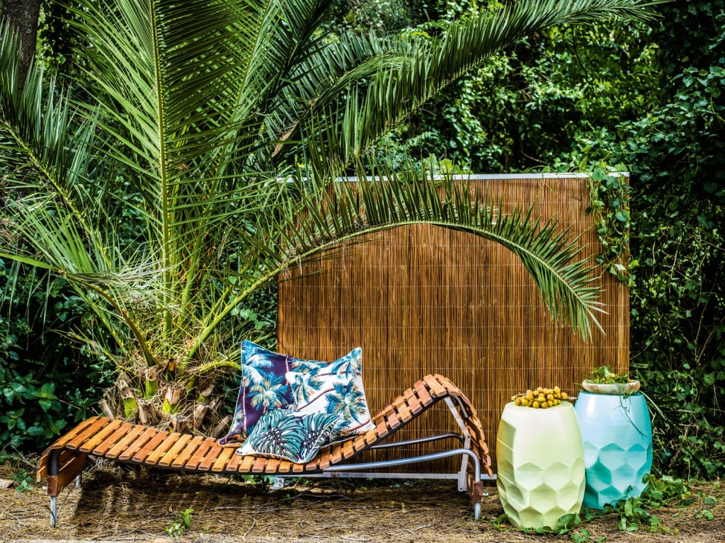 Adjustable day bed  and multi-function screen  in Natural. Designed  by Mark Snyders.  houseofbamboo.com.au Hex tables in Minty  Powder Blue and Pale Yellow, Oasis outdoor cushion in Palm Trees  and South Pacific.  escapetoparadise.com.au