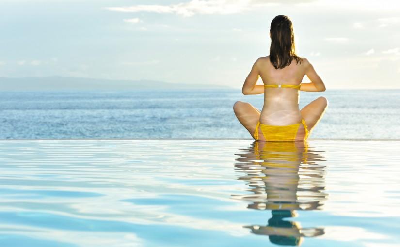 Woman doing yoga at poolside